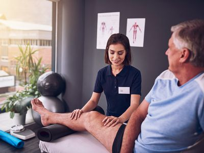 young physical therapist helping a male client