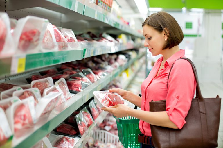Woman choosing meat in the grocery store