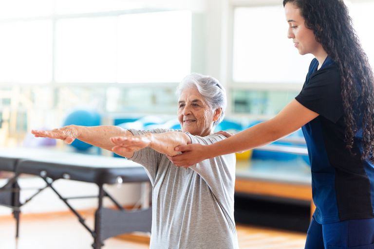 Elderly woman being helped by female occupational therapist