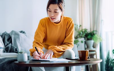 Woman sitting at a coffee table, working on paperwork