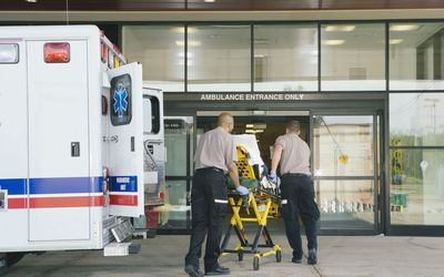 Paramedics taking patient from an ambulance to the hospital