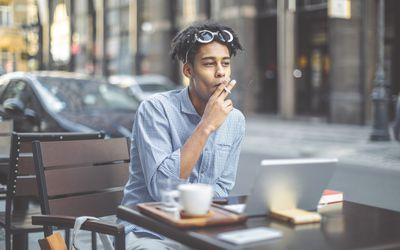 a man smoking outside at a cafe