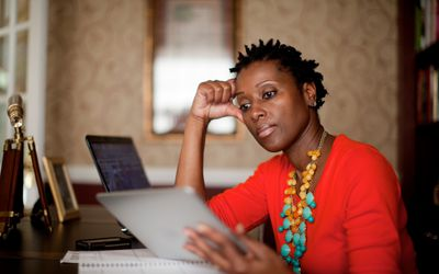Woman in home office with tablet looking at bills