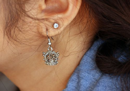 Close up of two earrings in a woman's ear