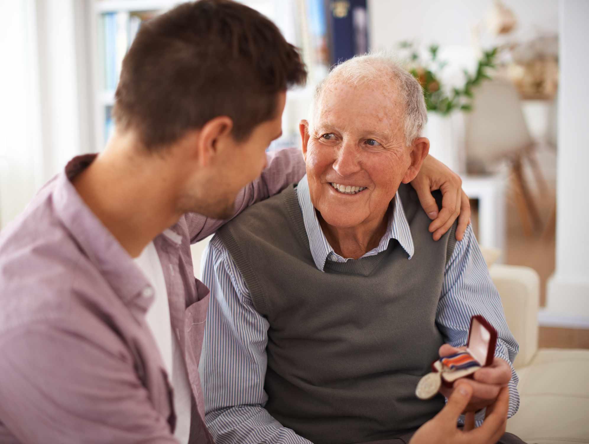 An older man showing his grandson a medal