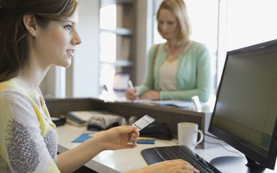 Receptionist inputting insurance information at computer