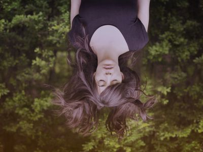 A woman upside down in the forrest