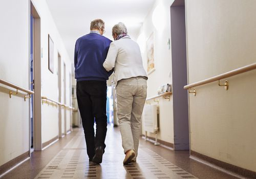 Man and woman walking down hallway of care facility