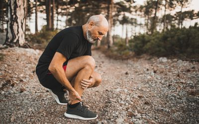 Calf muscle injury on running outdoors. Senior man holding knee by hands and suffering with pain. Sprain ligament or periosteum problem.