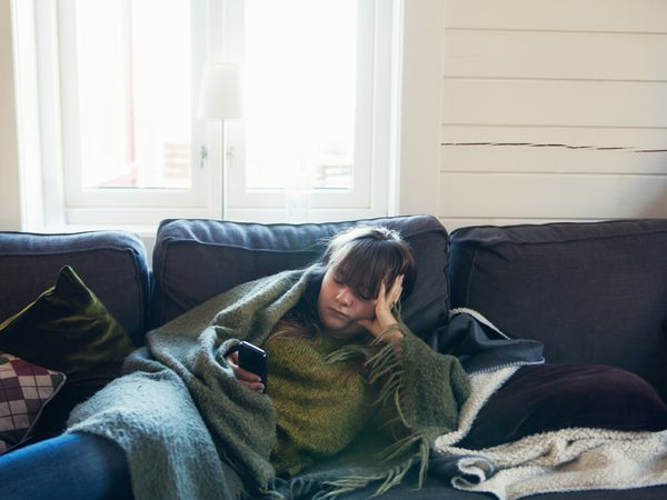 Woman sitting on the couch scrolling through her cell phone