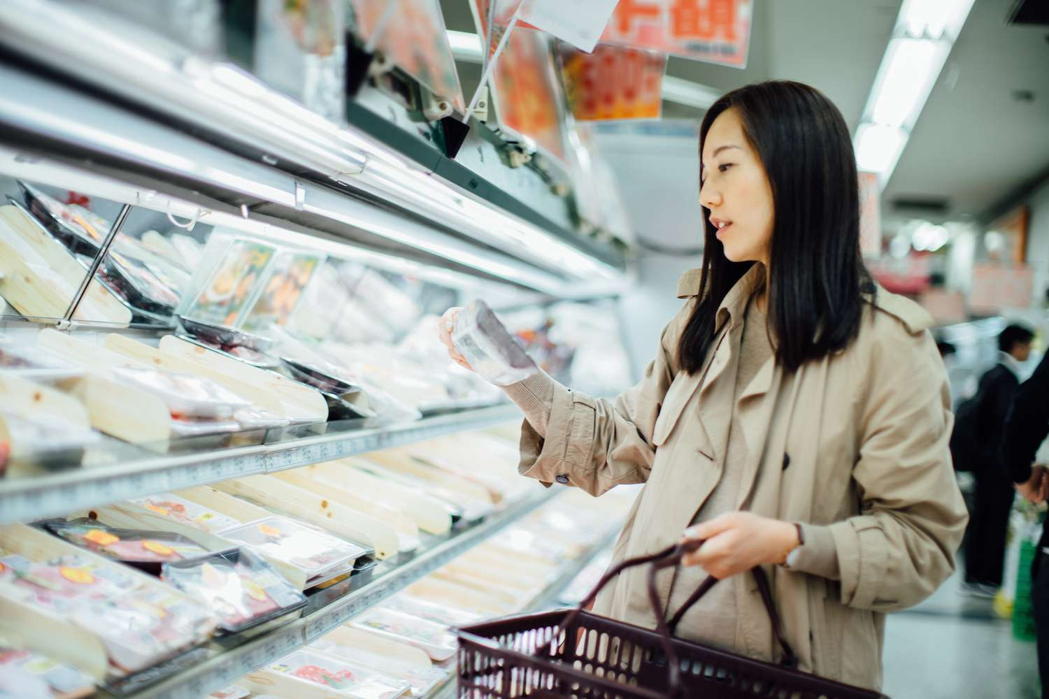 Young Asian woman grocery shopping and choosing fresh poultry in supermarket - stock photo