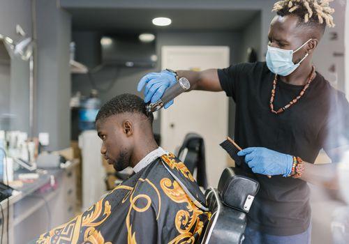 Black barber wearing a mask giving a man a haircut