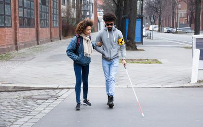 Blind person and friend cross street