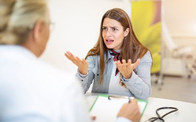 Upset patient sitting across a desk from a doctor
