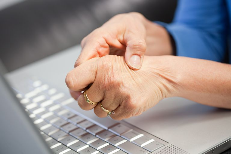 woman with arthritis lupus hand pain at laptop