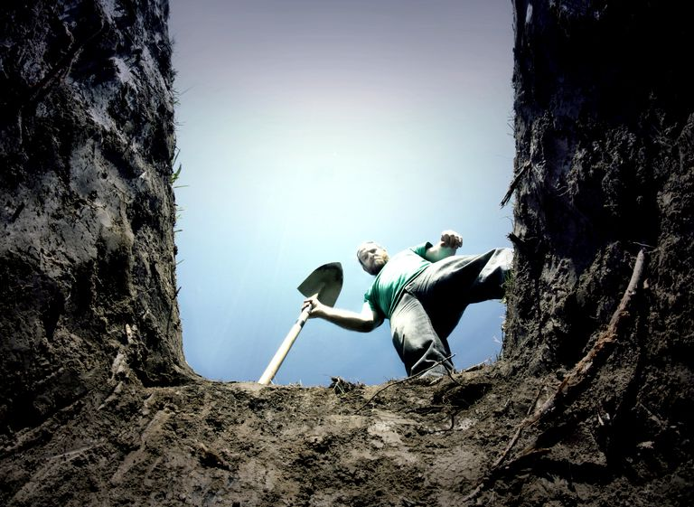 Gravedigger looking into gravesite