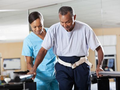 Photo of a woman helping a man with gait training.