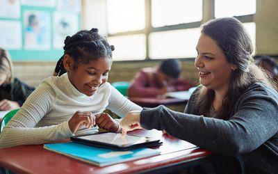 Teacher helps student learn using digital tablet