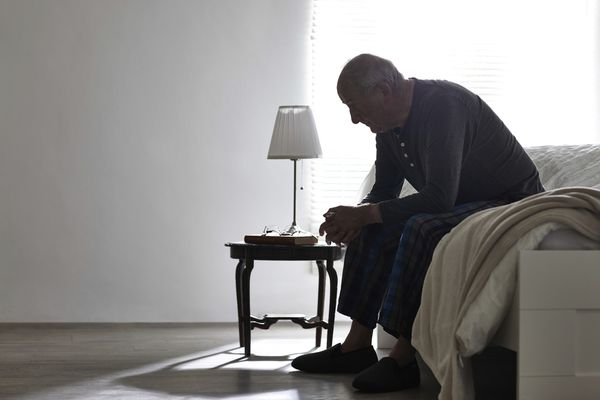 Elderly man sitting on bed looking serious
