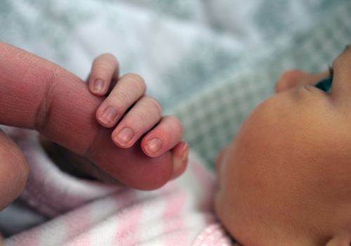A newborn holding mother's finger