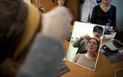 Cancer patient getting fitted with a head scarf