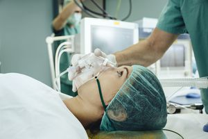 Patient with a respiratory mask on operating table
