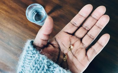 woman holding vitamin D supplement