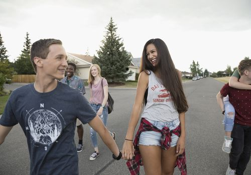 Teenage friends walking on neighborhood street