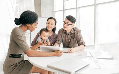 Couple with a baby filling out health insurance paperwork