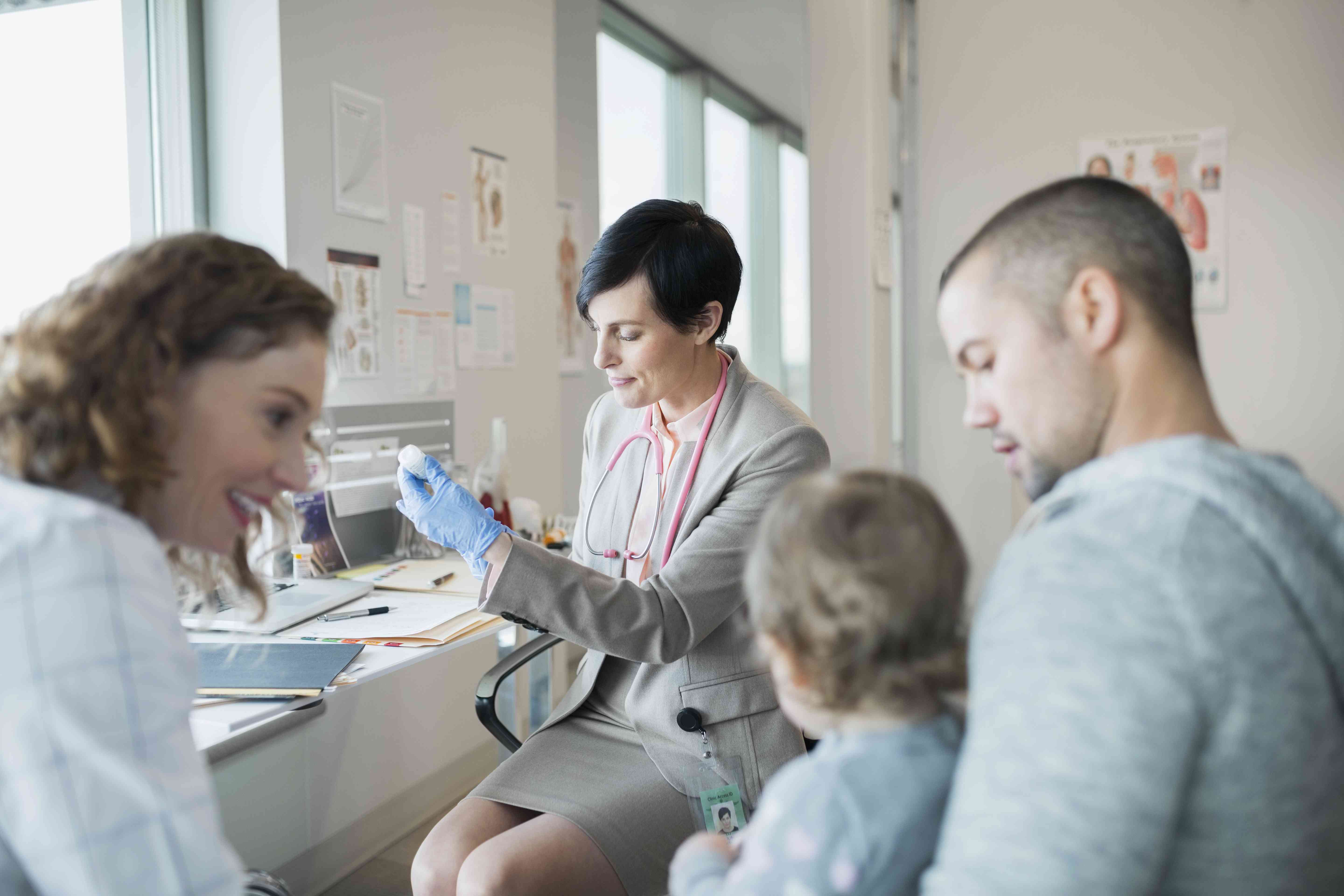 Parents holding baby girl while pediatrician prepares vaccination