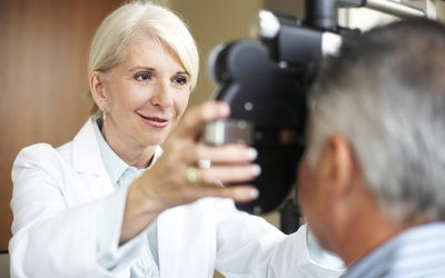 A female ophthalmologist uses a phoropter to check a male patient's eyes