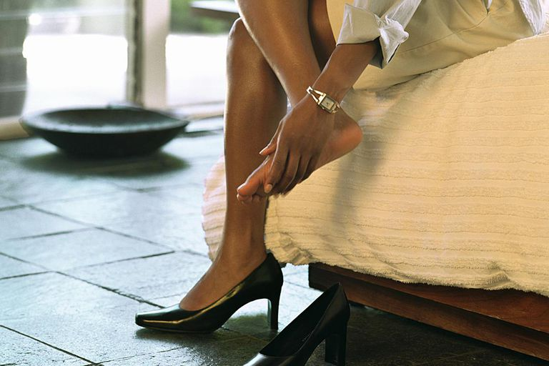 838f58cb38 Woman taking off high heels, rubbing feet, side view, low section