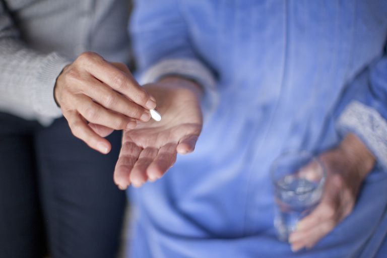 elderly person being given medication