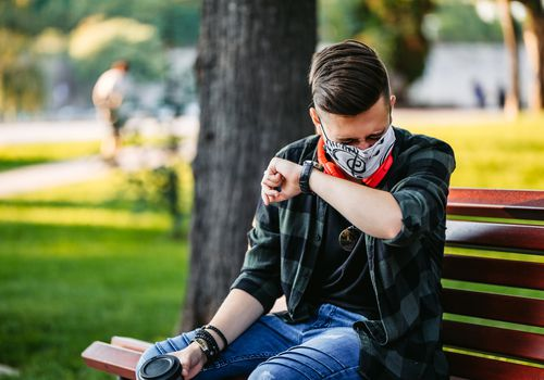 white male in flannel shirt wearing mask holding coffee sneezing on a bench