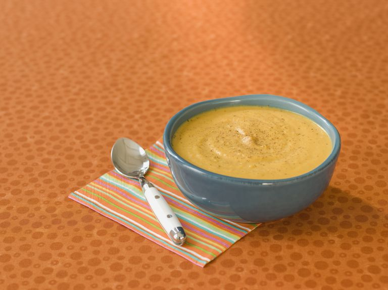 Pureed pumpkin soup in a bowl with a spoon and a napkin
