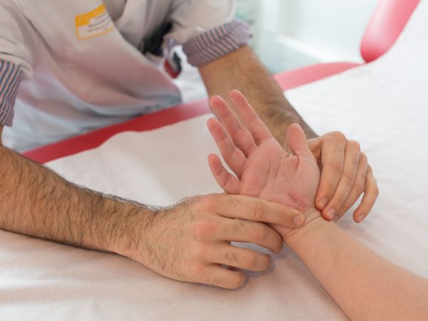 Rheumatologist examining the hand of a patient after surgery carpal tunnel.