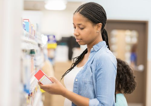 Woman reading label on over the counter medication
