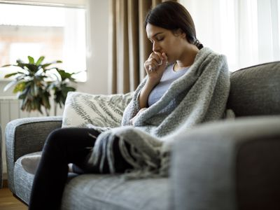 A young adult woman coughing into her hand while sitting on a couch with a blanket over her shoulders.
