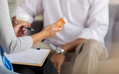 Female health care provider holding an orange medicine container while explaining the prescription to a male patient.