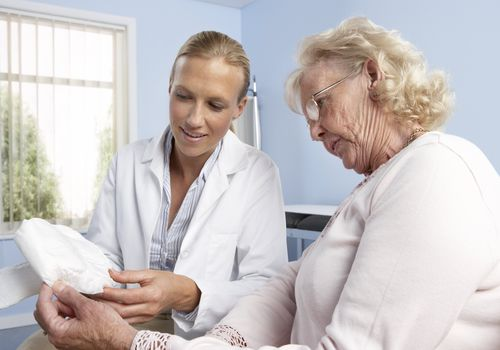 Doctor with elderly patient holding urinary incontinence pad