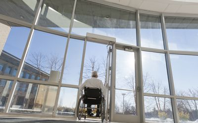 Man in a wheelchair leaving the hospital