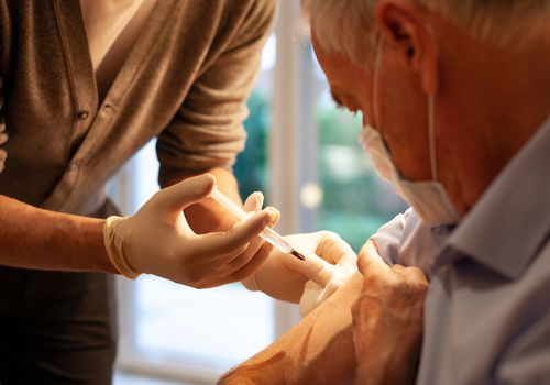 Older man receiving a vaccine shot while wearing mask.