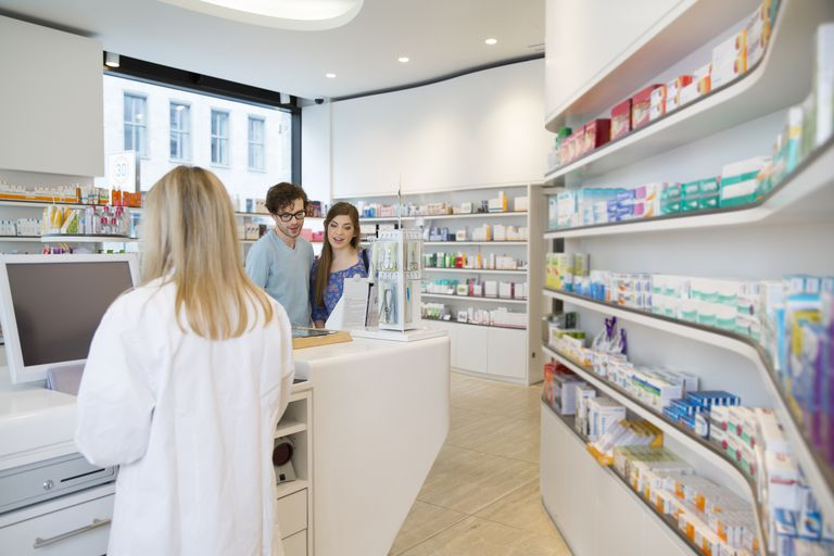 Customers and female pharmacist in a pharmacy