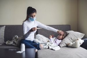 Mom checking the temperature of young child with the flu.
