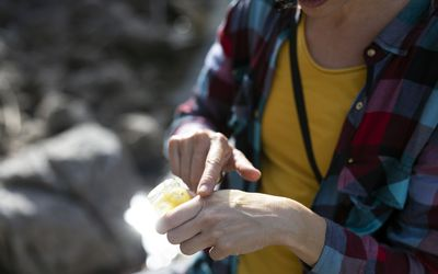 Closeup of Adult Woman Rubbing Hand Cream Into Her Hands Outdoors