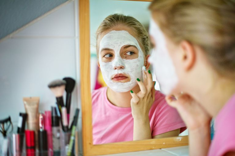 Teenage girl applying face mask