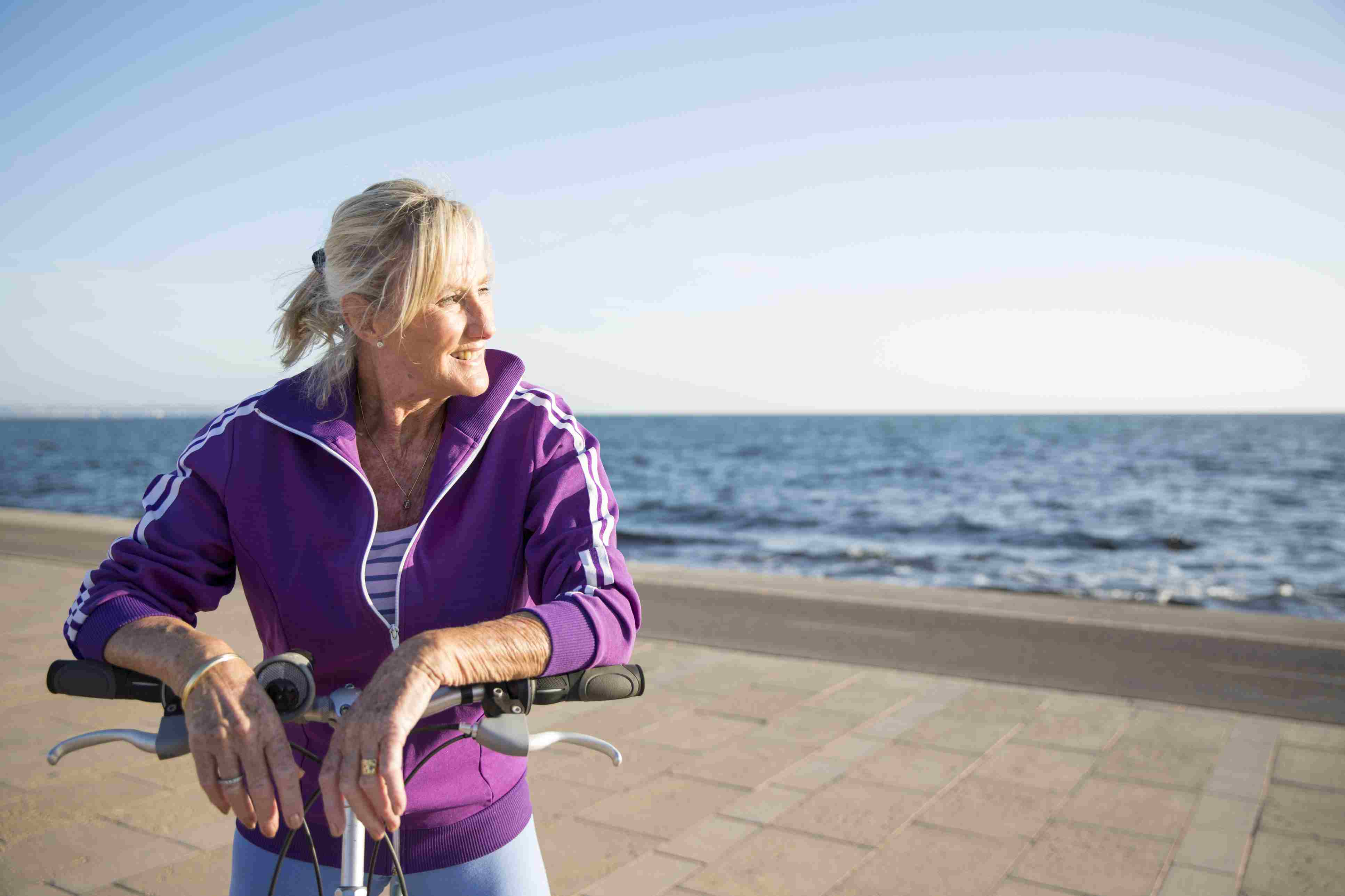 Woman resting on bike handle bars in front of the ocean.
