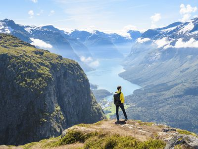Tourist admiring the view from the top of a mountain in Loen, Norway