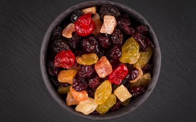 Close up of colorful assorted dried fruit in a black bowl on a black background.