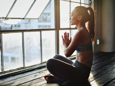 Seated woman in workout clothes with palms pressed together and eyes closed facing a window